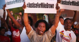 Demonstrators-outside-a-church-in-St-Louis-Missouri-protest-the-killing-of-teenager-Michael-Brown-in-Ferguson-AFP