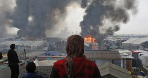 """People stand on a hill as smoke and flames rise from amidst the tents, after fires were started in the makeshift migrant camp known as """"the jungle"""" near Calais, northern France, Wednesday, Oct. 26, 2016. Firefighters have doused several dozen fires set by migrants as they left the makeshift camp where they have been living near the northern French city of Calais. (AP Photo/Thibault Camus)"""
