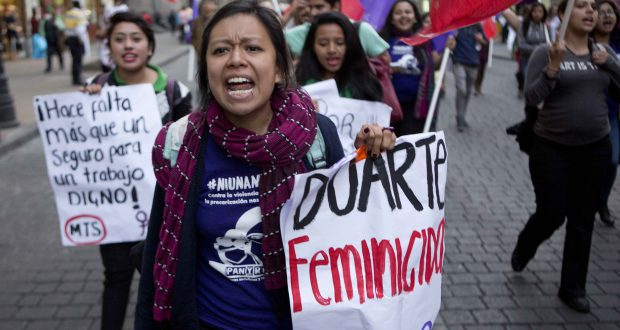 """A woman carries a banner  that reads in Spanish """"Duarte Femicide,"""" referring to the Gov. of the State of Chihuahua Cesar Duarte, during a protest against violence against women marking International Women's Day in Mexico City, Tuesday, March 8, 2016. International Women's Day celebrates women and their accomplishments, but it also offers a stark reminder of the gender divides in rights, representation and pay. (AP Photo/Eduardo Verdugo)"""